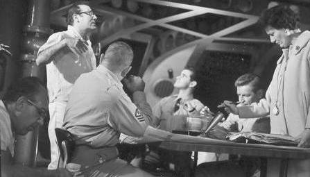 Irwin Allen discusses the upcoming take as a technician works foreground left and  script girl checks script.  Henry Kulk, Derrik Lewis and Richard Basehart seated.